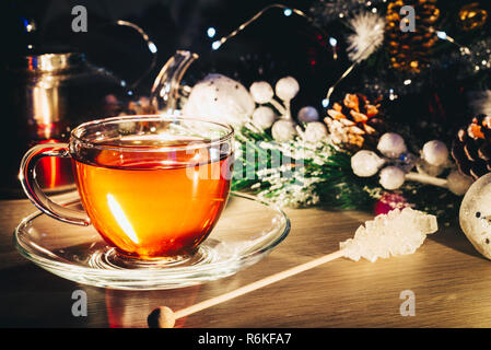 Still life with cup of black tea and sugar stick on the table - Stock Image