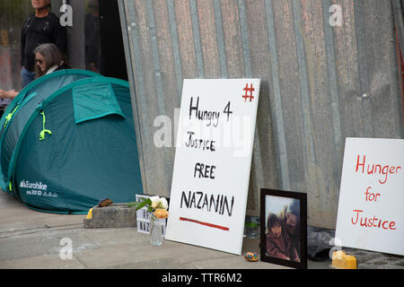 London, UK. 17th June 2019. Richard Ratcliffe on hunger strike in front of the Iranian embassy in London in protest of the detention of his wife Nazanin Zgahari in Iran over spying allegations. Richards family picture, boards and tent squeezed forward by large iron boards put up by embassy staff and builders. Credit: Joe Kuis / Alamy - Stock Image