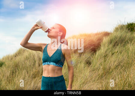 Sportswoman drinking water from a bottle after exercise in the sun - Stock Image
