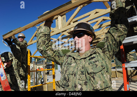 A Seabee holds up an A-frame as a hut is taken down. - Stock Image