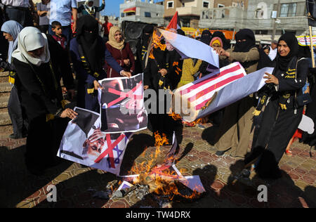 Palestinian women burn placards depicting U.S. President Donald Trump and Israeli Prime Minister Benjamin Netanyahu during a protest against Bahrain's workshop for U.S. peace plan, in southern Gaza Strip. - Stock Image