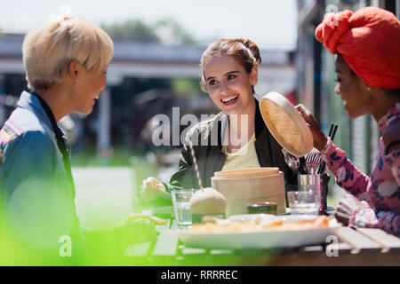 Young women friends eating dim sum lunch at sunny sidewalk cafe - Stock Image