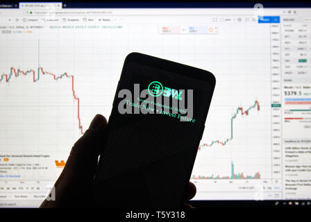 MONTREAL, CANADA - APRIL 26, 2019: BW.com cryptocurrency exchange logo and application on Android Samsung Galaxy s9 Plus screen in a hand over a lapto - Stock Image