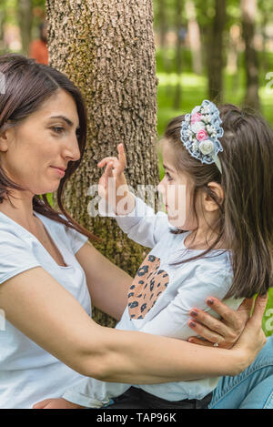 Young mom hugs and plays game with her daughter while embracing.Happy mother hugging her daughter with love and natural emotion. - Stock Image