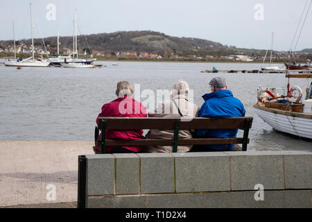 Three elderly people sitting on a bench on Conwy Quayside looking at the boats and yachts in Conwy harbour - Stock Image