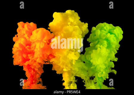 Orange, yellow and green paint in water, isolated on a black background. - Stock Image