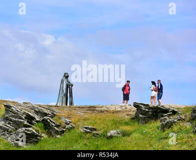 Tourists standing next to King Arthur an 8 ft bronze sculpture by artist Rubin Eynon, named Gallos Cornish word for Power, Tintagel castle,Cornwall,UK - Stock Image