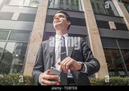 Close up of businessman next to skyscraper at downtown waiting for a meeting. Bottom view. - Stock Image