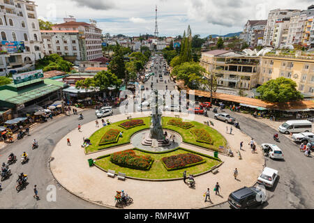Dalat, Vietnam - September 23, 2018: People walk and ride a motorbike at the central Market Square on September 23, 2018, in Dalat, Vietnam - Stock Image