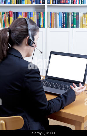 Rear view of a woman in a black blazer in front of her laptop with an empty screen, talking to someone, live or online video call concept template - Stock Image