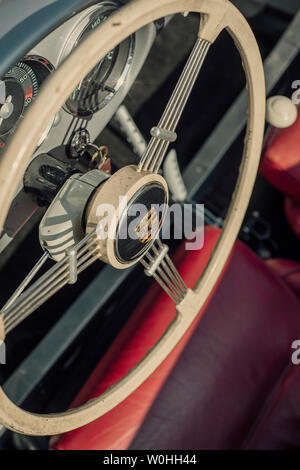 Steering wheel and dashboard of a vintage Porsche 550 Spyder sports car - Stock Image