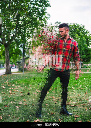 Side view of handsome young man in effect of diffusion with fragments flying away outside in city park - Stock Image