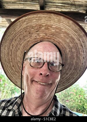 Man making funny face with giant hat - Stock Image