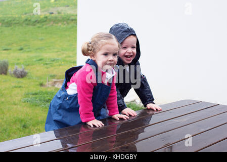 Children climbing on wet picnic table - Stock Image