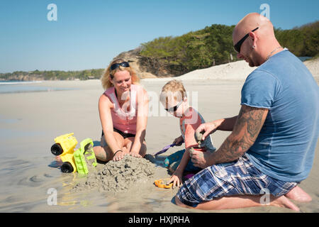 Family of 3 playing in the sand on the beach, Father, mother, toddler son. Riviera Nayarit, Mexico - Stock Image