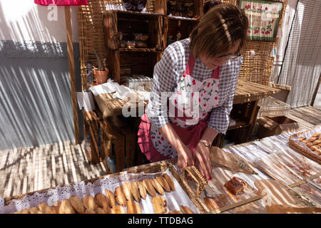 Local market trader serving cherry cake - Stock Image