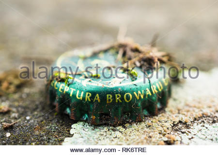 Poznan, Poland - February 7, 2019: Close up of a green metal beer cap laying on the ground in soft focus background. - Stock Image