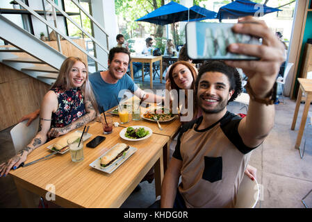 Man taking selfie with friends - Stock Image