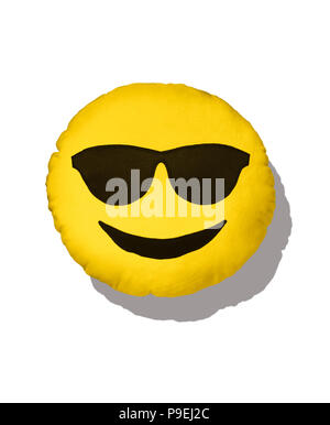 A colourful shot of the sunshine Emoji cushion with sun glasses. - Stock Image