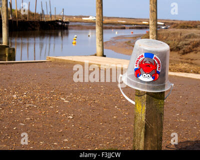 A clear plastic crabbing bucket upside down on a post in Blakeney, Norfolk. - Stock Image