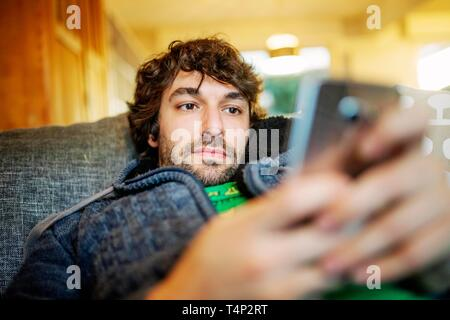 Young man lies relaxed with smartphone on sofa, Germany - Stock Image