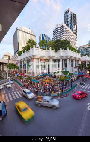 High angle shot of Ratchaprasong Intersection and Erawan Shrine in Bangkok, Thailand, with motion blurred cars driving past in busy traffic. - Stock Image