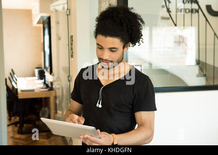 Young man using digital tablet - Stock Image