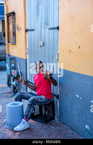 Young African-American street musician boy drumming on a plastic bucket on Bourboun Street, New Orleans French Quarter New Orleans, Louisiana, USA - Stock Image