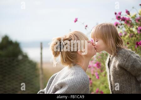 Mother kissing son in organic garden - Stock Image