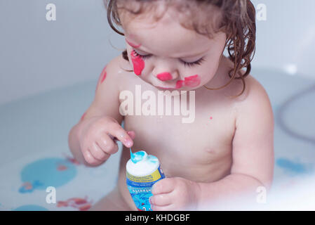 Little girl playing in bathtub - Stock Image