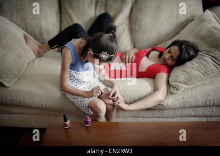 Girl applies nail polish to her mother's nails. - Stock Image