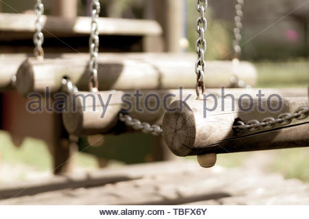 Wooden bridge hanging on chains of a playground - Stock Image