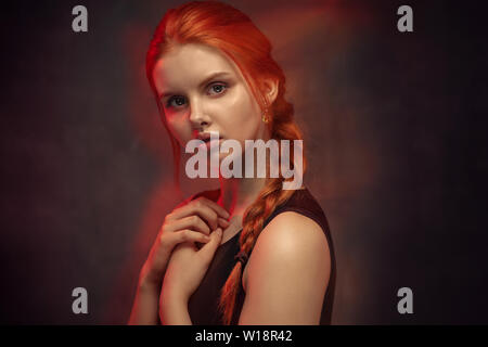 Beauty portrait of redhead girl with long braid and crossed hands. Magical glow of red light around the model - Stock Image
