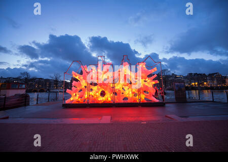 Amsterdam during Amsterdam Light Festival with color changing artwork 'Rhizome House'in red orange of 'DP Architects' with beautiful sky, river Amstel - Stock Image