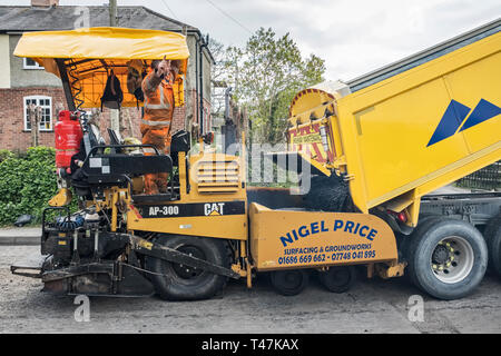 Presteigne, Powys, Wales, UK. An asphalt paver or paving machine laying fresh tarmac on a road in the town, being refilled from a tipper truck - Stock Image