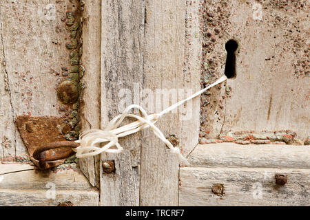 Ancient door closed with a rusty hinge and a piece of rope - Stock Image