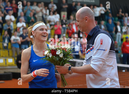 Prostejov, Czech Republic. 21st Apr, 2019. Czech tennis player Lucie Safarova receives a bouquet from captain Petr Pala, as she officially ends her career, after winning with Barbora Krejcikova the play-off doubles game against Canada's Dabrowski-Fichman in the Fed Cup match between Czech Republic and Canada, in Prostejov, Czech Republic, on April 21, 2019. Credit: Lubos Pavlicek/CTK Photo/Alamy Live News - Stock Image