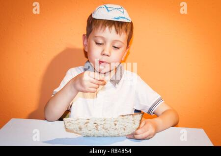 Cute Caucasian Jewish child with a kippah on his head eating the traditional matzo bread. Jewish Passover Pesach concept image. - Stock Image