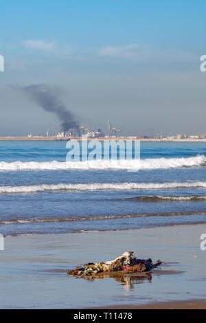Air and ocean pollution as smoke rises over the horizon with clothing and rope debris washed up by the Atlantic Ocean onto a sand beach in Morocco - Stock Image