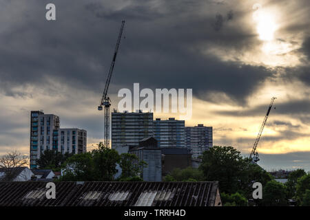 London, England, UK - June 1, 2019: The sun sets behind the remaining tower blocks of the Alma Estate during regeneration of the housing in the Ponder - Stock Image