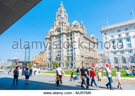 Glorious sunshine at the Pier Head on the banks of the River Mersey, people walking in the sunshine in front of the Liver Building, on a sunny Bank Holiday Weekend, Liverpool, England UK Europe - Stock Image