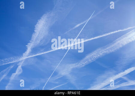 Abstract patterns of vapour trails in the blue sky, sometimes known as contrails or condensation trails. - Stock Image