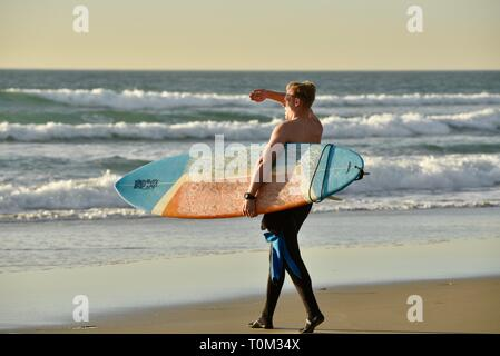 Attractive man walking toward ocean water at sunset with surfboard tucked under his arm and blocking sun with arm, Pacific Beach, San Diego, CA, USA - Stock Image