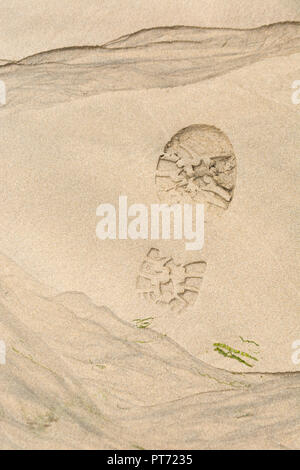 Footprint / boot print in wet sandy beach. - Stock Image