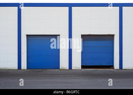 White Industrial warehouse with blue door for trucks - Stock Image