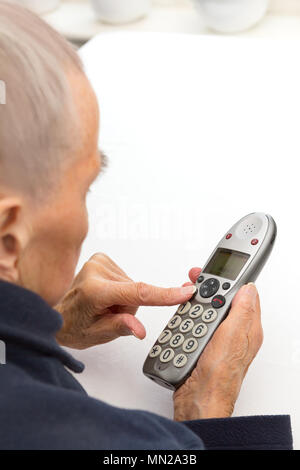 Very old woman with decreasing vision pressing the buttons of a landline telephone especially for seniors with a larger keypad - Stock Image