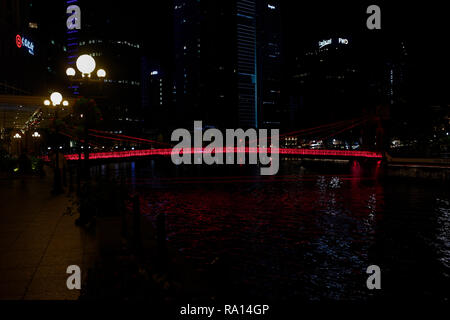 The Cavenaugh bridge, the only suspension bridge on the Singapore river, illuminated in red at night. - Stock Image