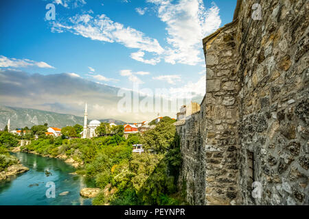 The river Neretva flows by the ancient wall surrounding the old town section of Mostar, Bosnia - Stock Image