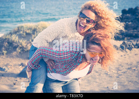 Beautiful crazy caucasian people young women carry on eachother having a lot of laughs and fun for friendship - outdoor leisure activity and vacation  - Stock Image
