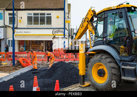 Road Repair team spreading Tarmac for resurfacing a road after cable laying - Stock Image